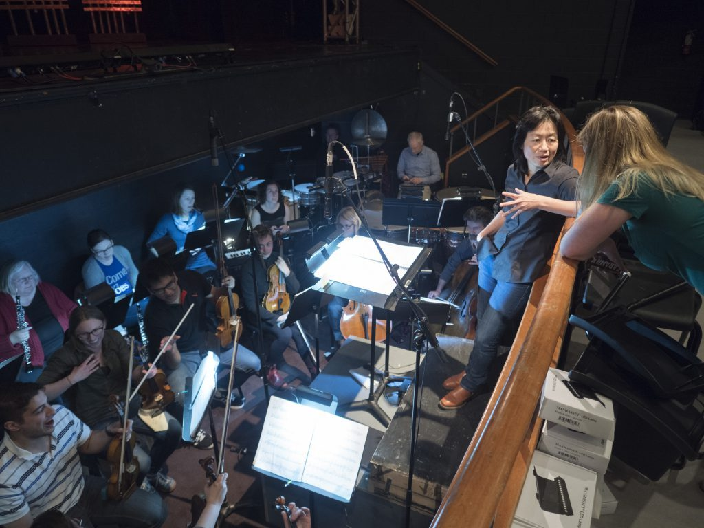 Maestro Judith Yan in the orchestra pit during rehearsals for Dead Man Walking, 2017